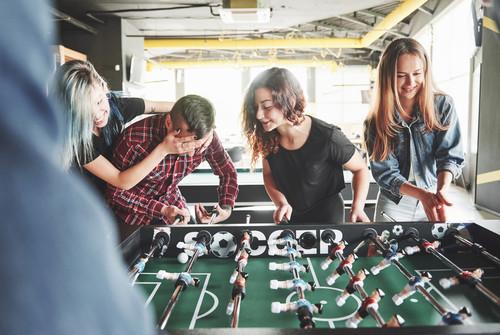 amigos jugando en una mesa de futbolín profesional de madera